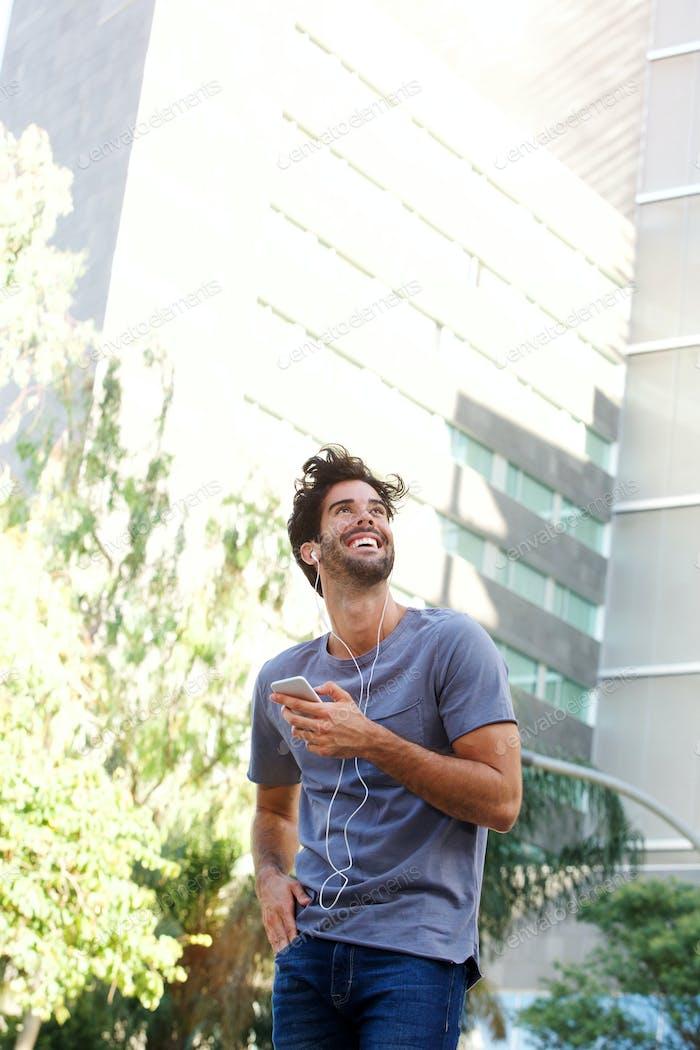 Laughing man standing on urban street holding smart phone