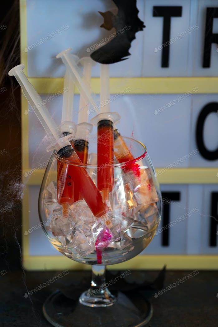 Bloody Mary Cocktail in Spritze mit Netz für Halloween Party Feier. Schwarzer Stein Hintergrund