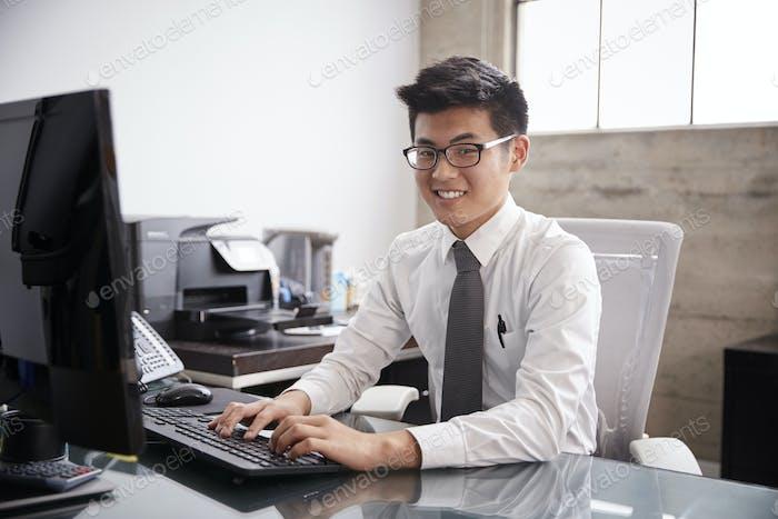 Junge asiatische Geschäftsmann mit einem Computer, lächelnd Kamera