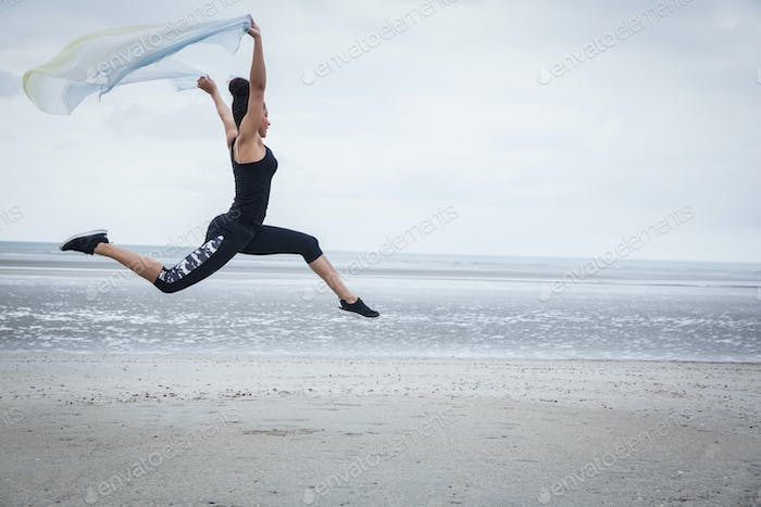 Fit girl leaping with scarf at the beach