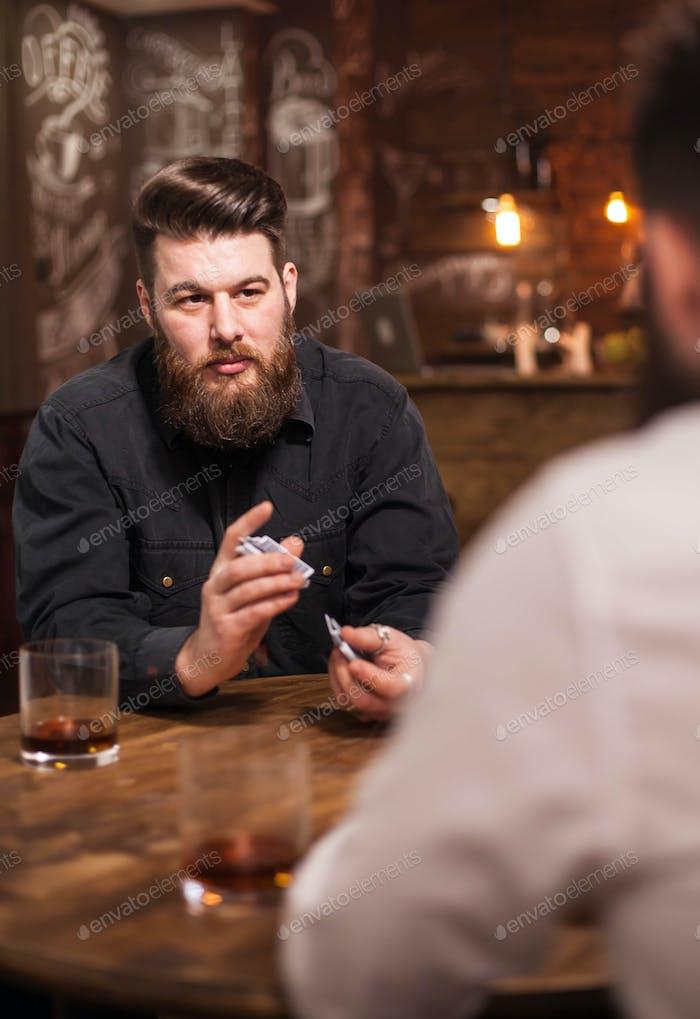 Hübscher bärtiger Mann Blick auf seinen Freund und shuffle Karten