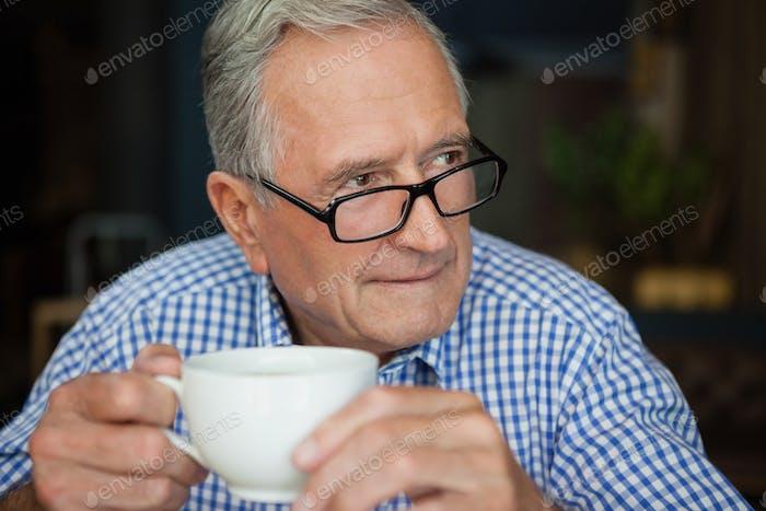 Thoughtful senior man sitting at cafe