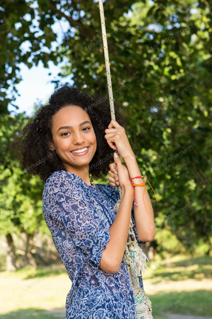 Pretty young woman in swing on a summers day