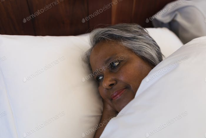 Close-up of a thoughtful senior African American woman lying in her bed at home