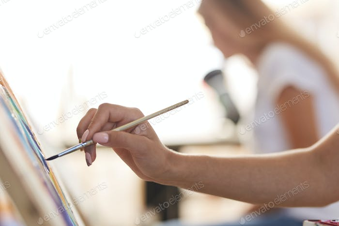 Girls hand holds a paint brush. Process of painting picture at the easels in the art studio