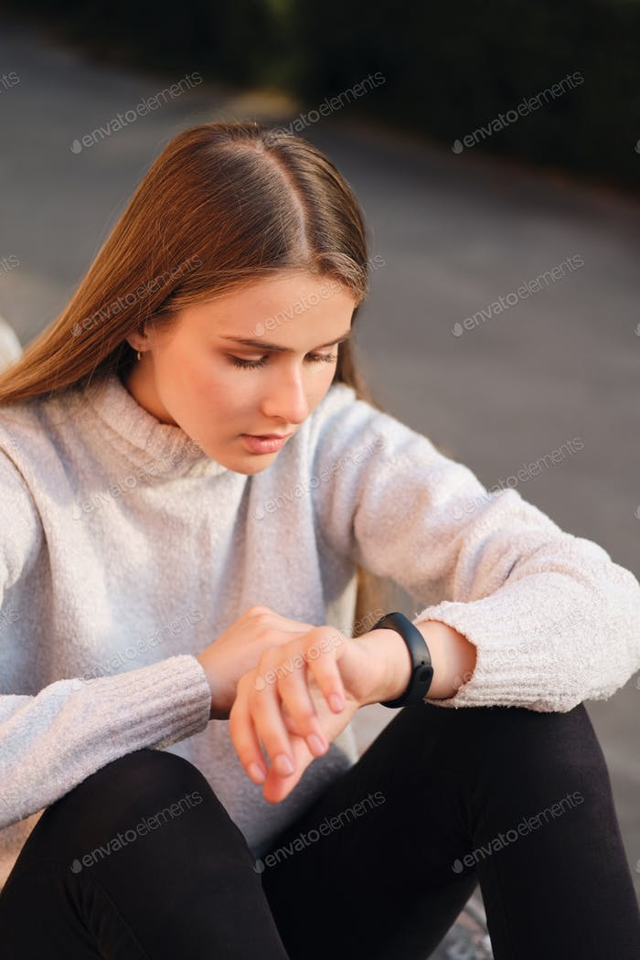 Attractive student girl in cozy sweater thoughtfully using health watch during study break outdoor