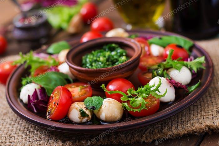 Салат Капрезе помидоры и моцарелла с базиликом и травами на коричневой тарелке