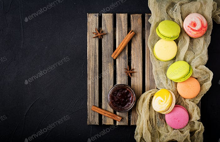 Bunte Makronen und ein Glas Honig auf einem hölzernen Hintergrund. Flache Lag. Ansicht von oben