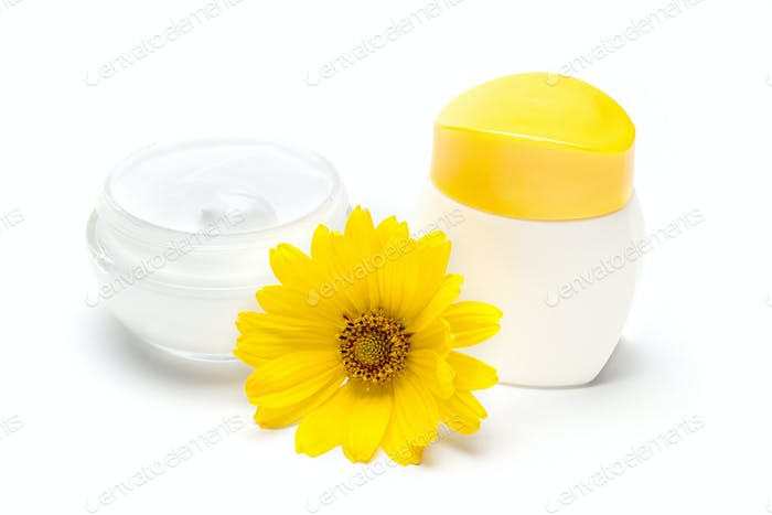 Jars of natural skin care cream with yellow flower