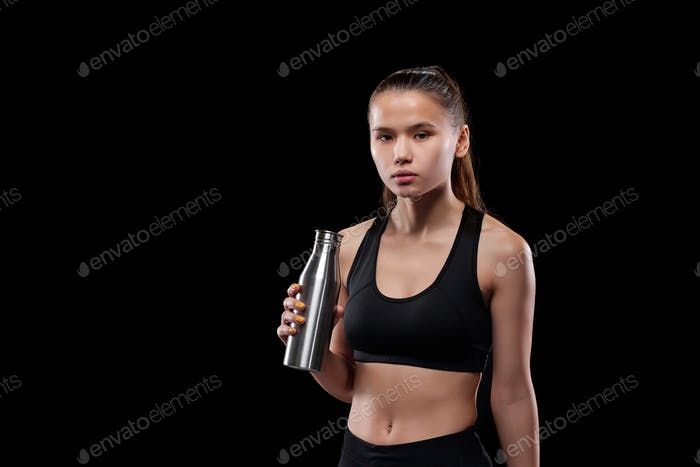 Young sportswoman with metal bottle drinking water after workout