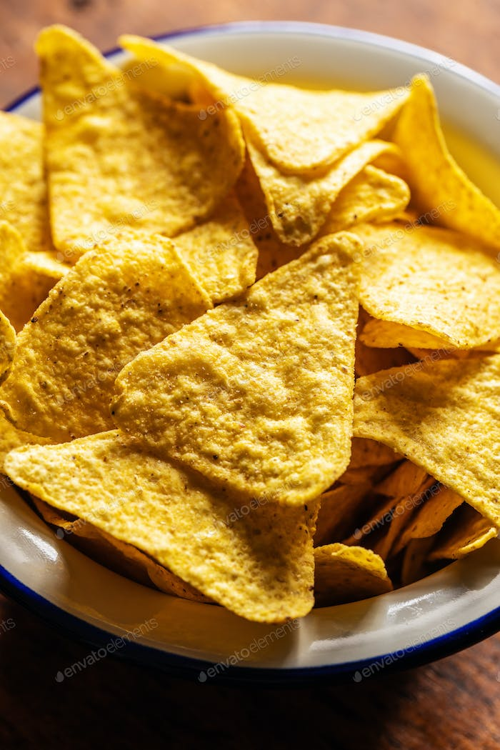 Salted tortilla chips. Yellow nachos triangle in bowl.