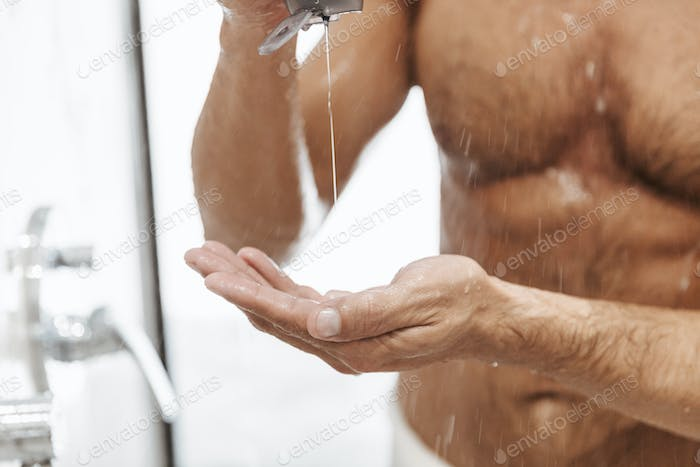 Close up of a naked man putting shower gel