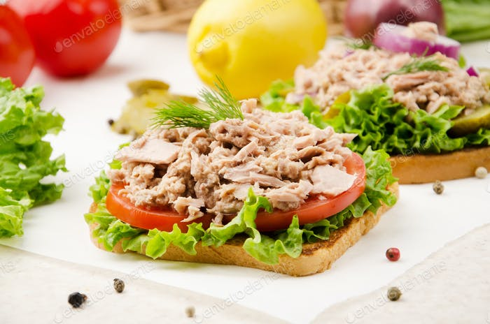 Tuna sandwiches with lettuce tomatoes and onions on parchment paper