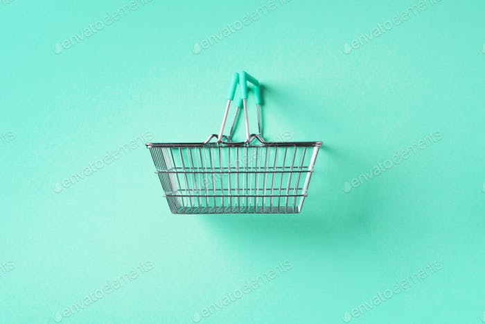 Top view of supermarket shopping basket on trendy green background. Black friday sale concept. Copy