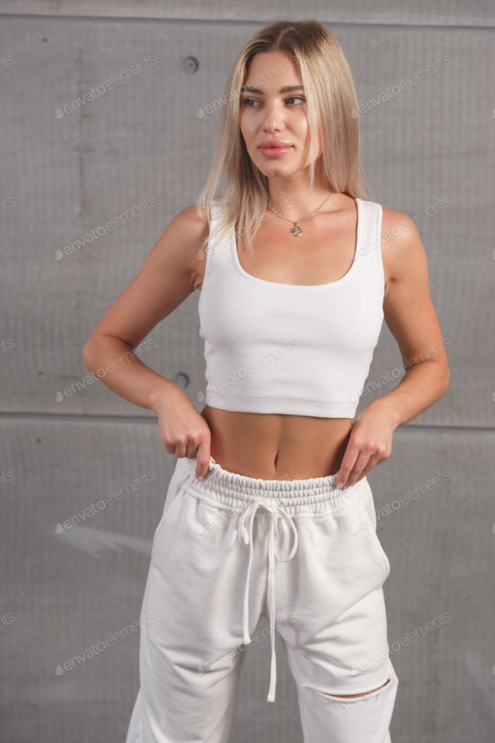 Fit and healthy blonde woman. Portrait of a sexy girl in stylish white sportswear in the studio