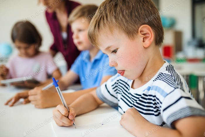 A group of small school kids with teacher in class writing