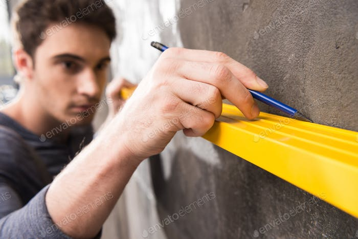 Handsome young laborer with pencil measuring wall with level tool, renovation concept