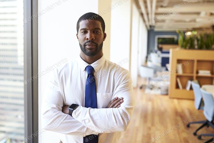 Portrait Of Businessman Wearing Smart Watch In Modern Office Standing By Window