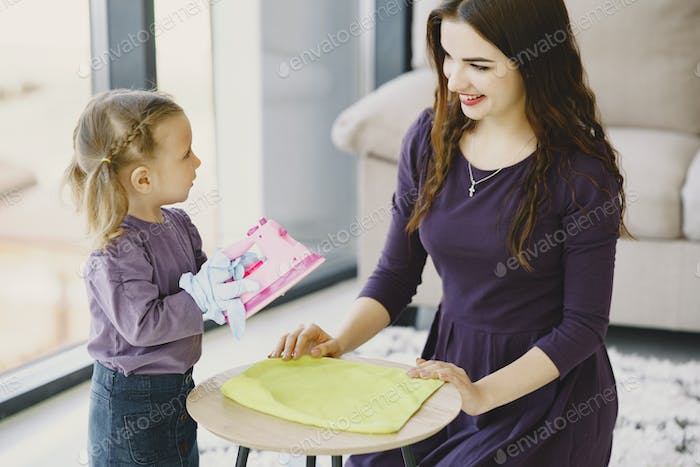 Mother with daughter playing with toy iron