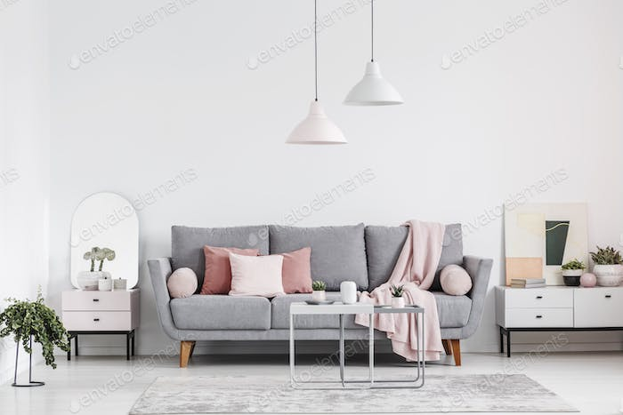 Real photo of an elegant living room interior with a grey sofa,
