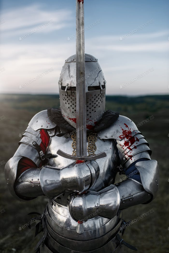 Knight in armor and helmet poses with sword