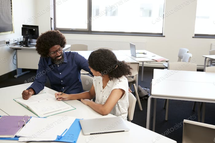 High School Tutor Giving Female Student One To One Tuition At Desk  In Classroom