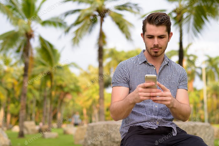Happy man relaxing at the park while using mobile phone