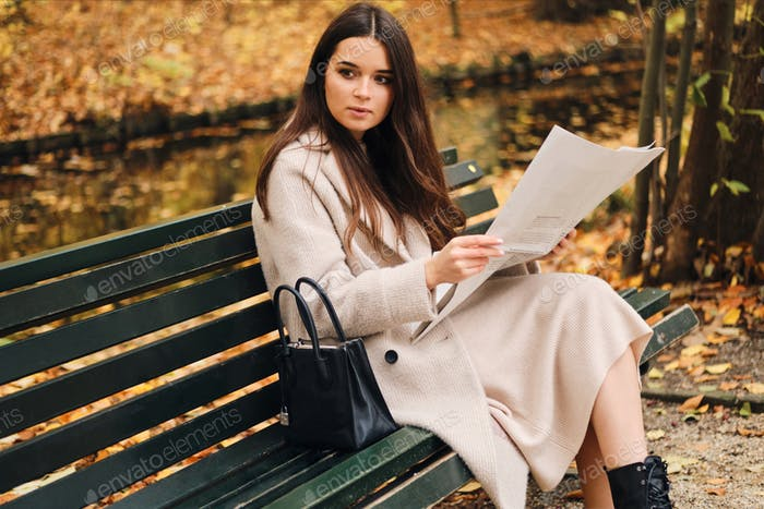 Beautiful stylish brunette girl with newspaper resting on bench in autumn park
