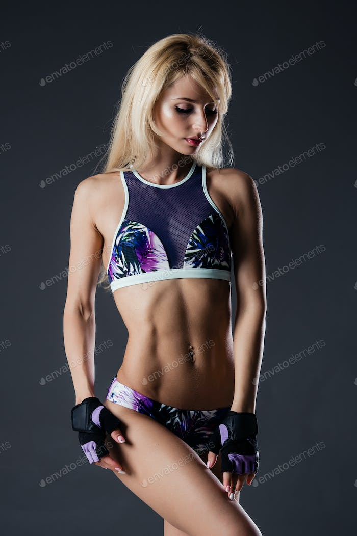 Portrait of sexy young woman with her hands on hips. Fitness female with muscular body ready wearing