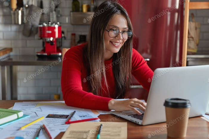 Glad brunette business lady keyboards on laptop computer, works freelance, surrounded with documents