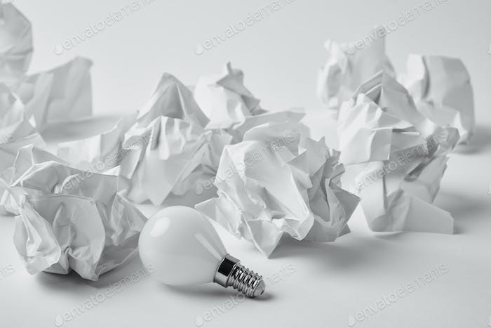close-up shot of energy saving light bulb with crumpled papers on white
