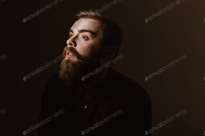 Sepia portrait of a pensive man with a beard and stylish hairdo dressed in the black shirt on the