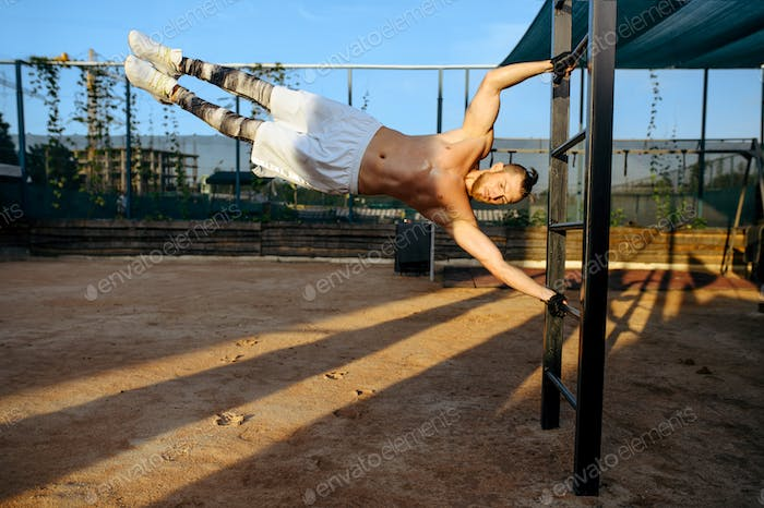 Man hanging horizontally on a bar, street workout