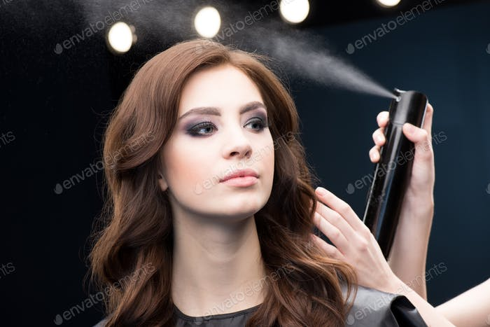 Hairdresser fixing hair of gorgeous woman with hairspray
