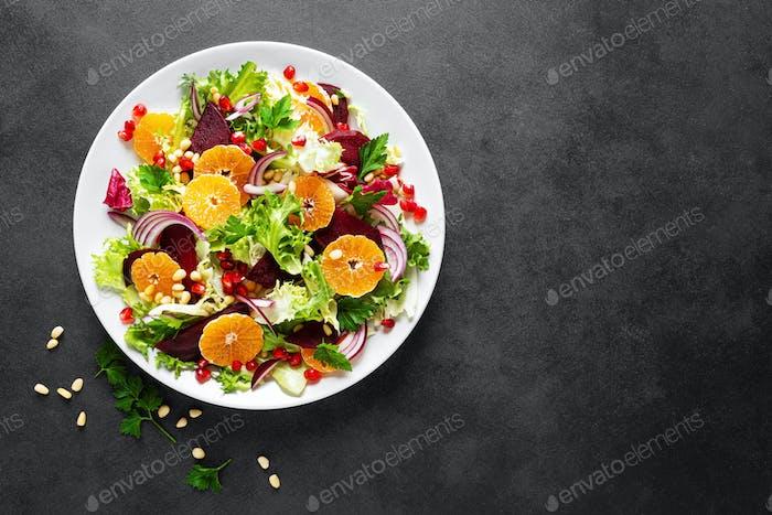Weihnachtssalat mit gekochten Rüben, roten Zwiebeln, Mandarinen, Granatapfel, Petersilie, Pinienkernen und Salat
