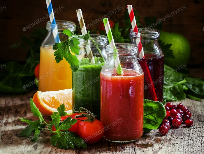Mix of healthy fruit and vegetable juices in small bottles with colored striped straws