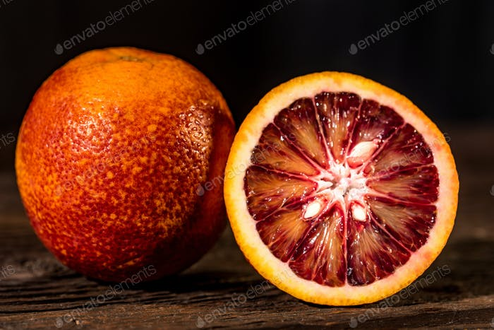 Whole and cut ripe juicy Sicilian Blood oranges