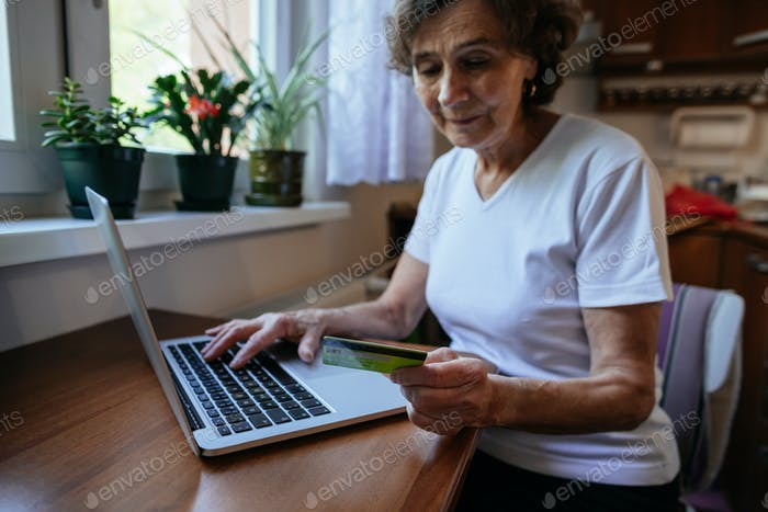 Elderly woman holding credit card buying online on internet.