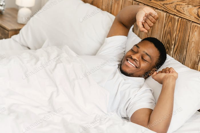 Rested Black Man Waking Up Lying In Bed At Home