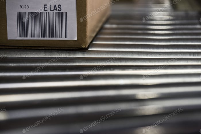 Close up of shipping labels with bar codes on cardboard boxes sitting on a motorized conveyor roller