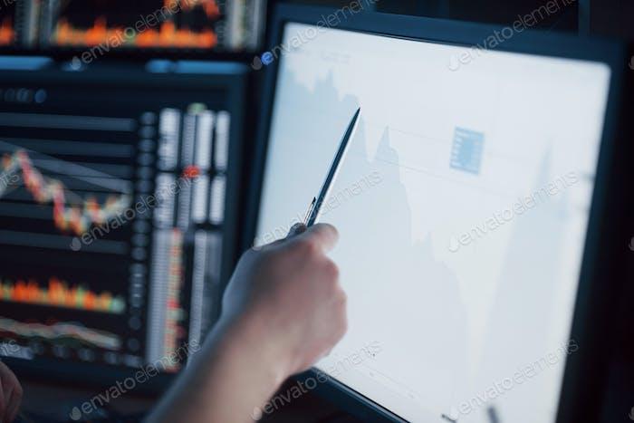 Analizando datos. Primer plano del joven empresario apuntando a los datos presentados en el gráfico con pluma
