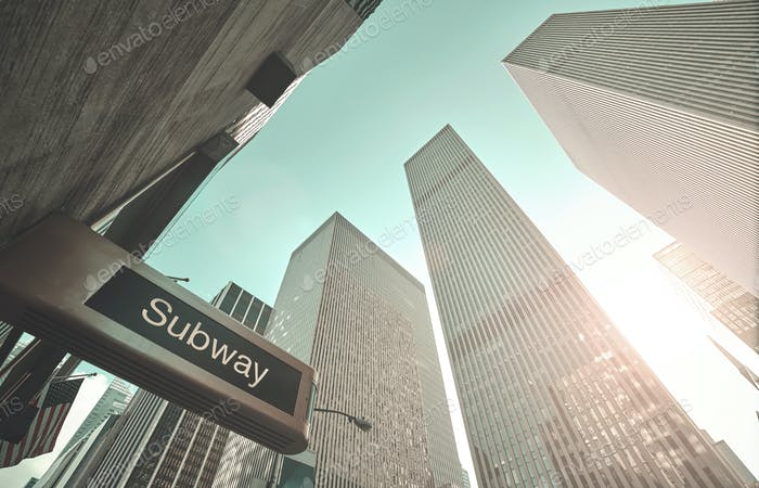 Subway entrance sign and New York skyscrapers.