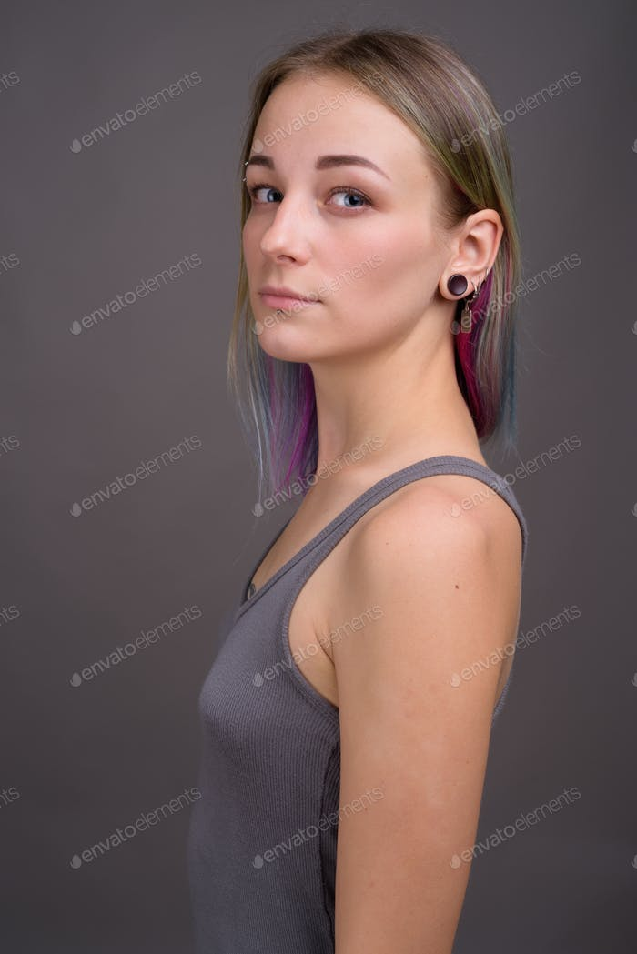 Young beautiful rebellious woman with multicolored hair against
