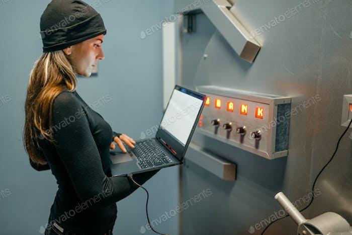 Weiblicher Räuber mit Laptop versucht, den Tresor zu öffnen