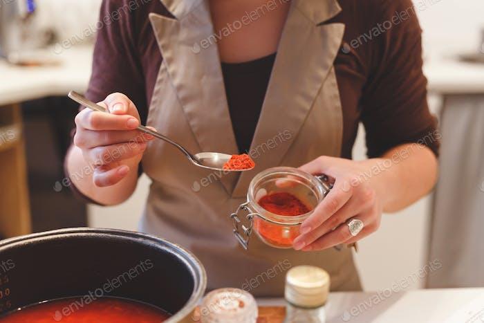 Weibliche Koch fügt Paprika Gewürze beim Kochen Tomatensuppe.Nahansicht auf Löffel mit rotem Pfeffer.