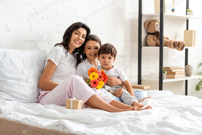 happy mother embracing children while sitting in bed with mothers day bouquet and gift box