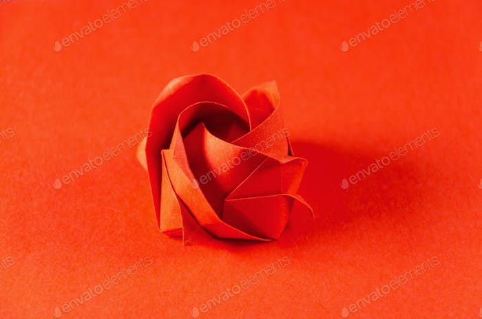 Red origami rose on red background