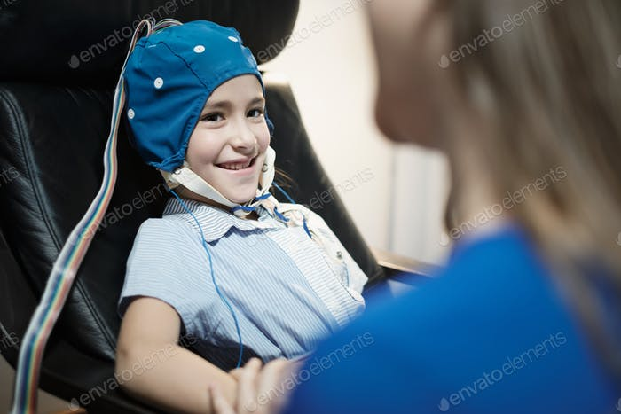 Portrait of Smiling Autistic Girl Undergoing an EEG Examination