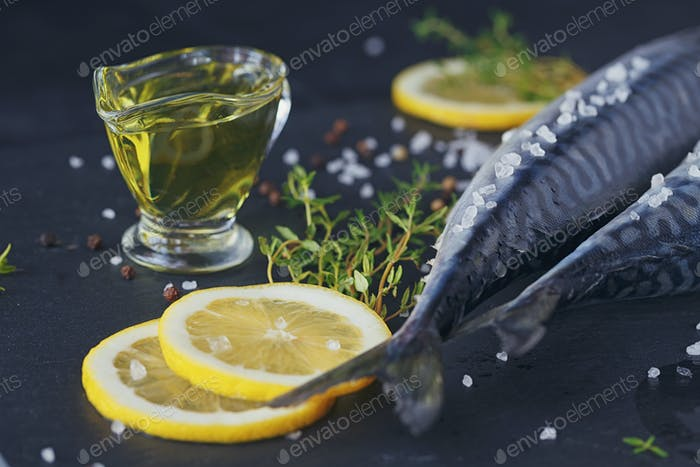 Fresh raw fish mackerel and ingredients for cooking on a dark background in a rustic style.