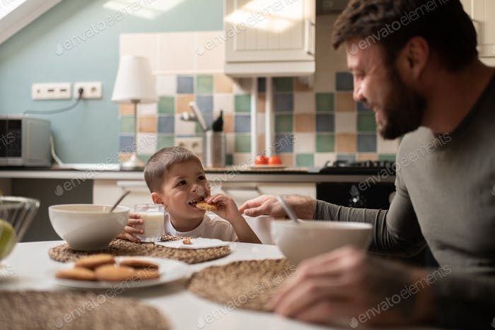 Little boy having breakfast with father